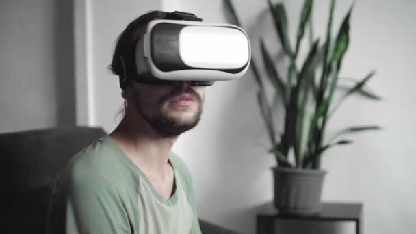 Young bearded hipster man using his VR headset display for virtual reality game or watching the 360 video while sitting on sofa at home in the living room. VR Technology.
