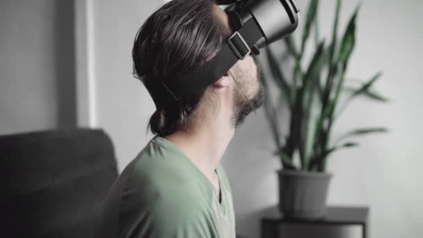 d6a2f8990bcc stock footage. Young bearded hipster man start using his VR headset display  with headphones for virtual reality game