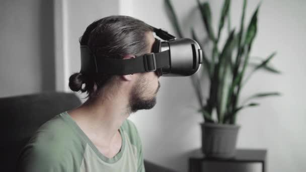 junger bärtiger Hipster-Mann, der sein vr-Headset-Display für Virtual-Reality-Spiele benutzt oder sich das 360-Video ansieht, während er zu Hause auf dem Sofa im Wohnzimmer sitzt. vr-Technologie.