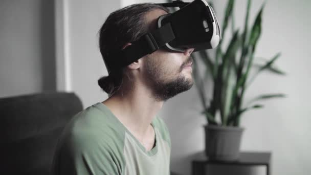 Young bearded hipster man using his VR headset display for virtual reality game or watching the 360 video and and was frightened by something while sitting on sofa at home in the living room.