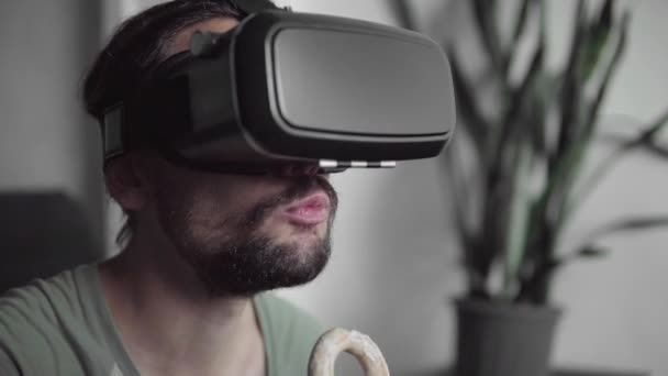 Young bearded hipster man using his VR headset display for watching the 360 video while sitting on sofa and eating cookies at home in the living room. VR Technology.