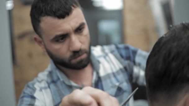 Close-up of barber cuts the hair by scissors at barbershop. Hairdressers hands at working process. Barber making haircut of attractive bearded man in barbershop. Hairdresser at work. Beauty saloon.