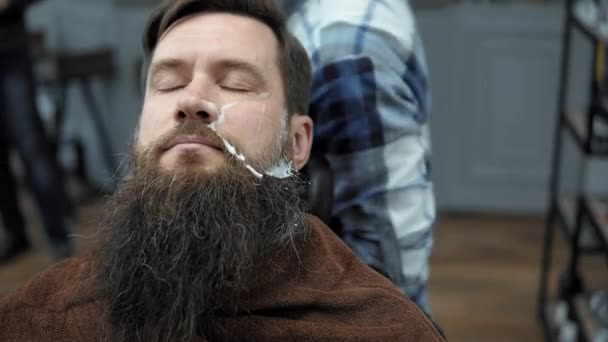 Barber shaves men with a long beard with straight razor blade in s hair salon or ...