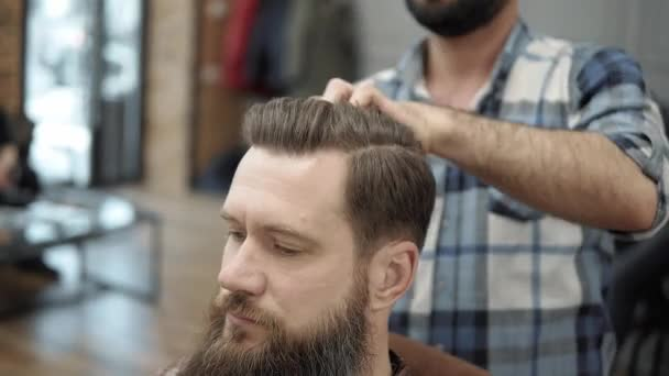 Close-up of barber doing styling with a handsome man with a long beard. Hairdressers hands at working process. Barber making haircut of attractive bearded man in barbershop. Hairdresser at work.