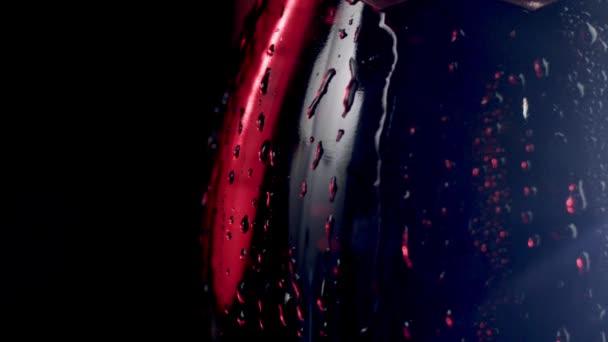 Einschenken von Rotwein aus der Flasche Makro Super Zeitlupe Schuss, schwarzer Hintergrund