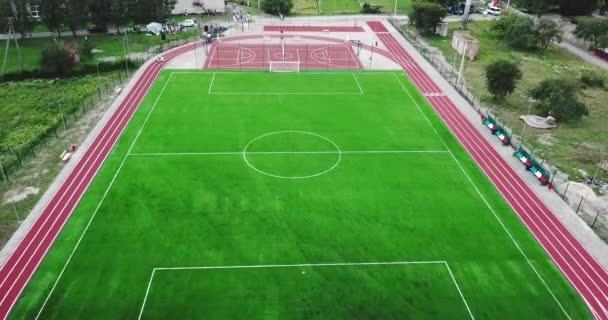 Leerer Spielplatz Stadion mit rotem Sportplatz für große Tennis-Basketball und grüne Fußball-Fußballplatz und Laufwege.