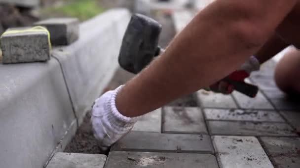 Kezében egy építő, ő narancssárga kesztyűs kezét egy kalapáccsal szóló új külső Térburkolatok gondosan elhelyezése egy helyzetben a leveled és raked talaj alap felszerelése. Homok Alapítvány. Épület.