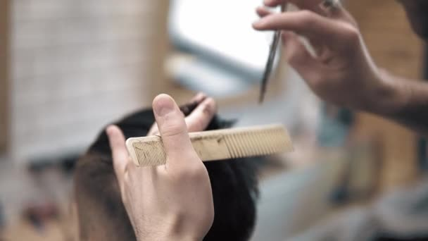Close up on Mens hairstyling and haircutting in a barber shop or hair salon using scissors and hair dryer. Grooming the hair. Barbershop.