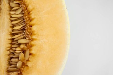 Fresh sweet orange melon on the white plate as a background with a selective focusing. Useful and vitamin-rich food. Vegeterian.