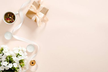 Flatlay composition with gift box, flowers bouquet, ribbon, candles, tea cup on pastel pink background. Flat lay, top view, copy space. Love and romance concept.
