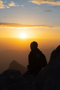 Silhouette of person watching sunrise form top of mountain
