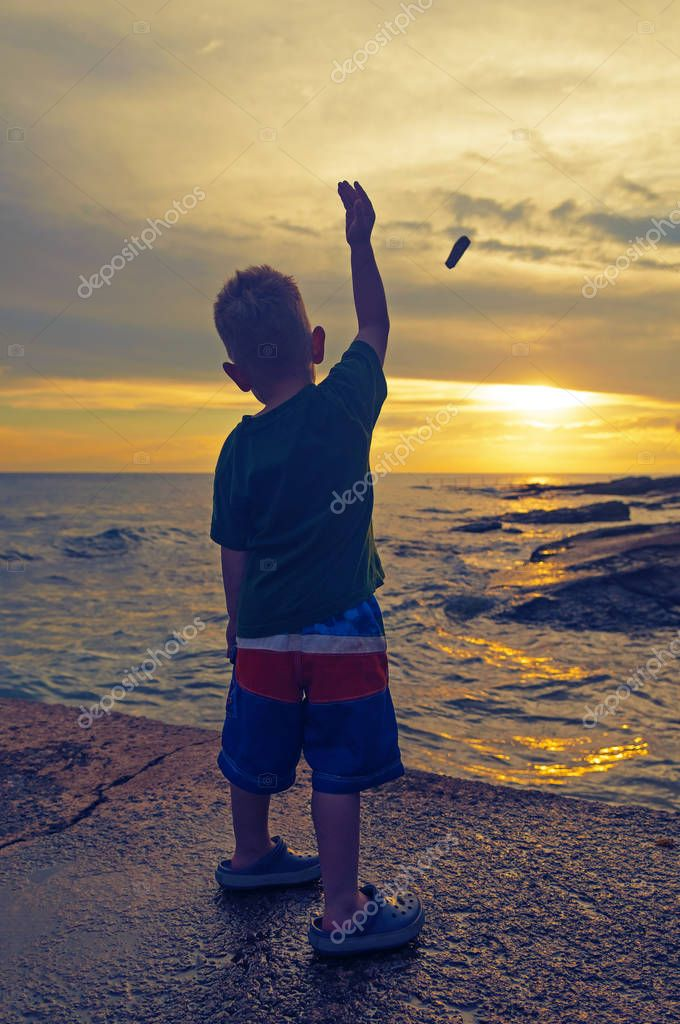 Little boy tossing a stone in the sea at sunset