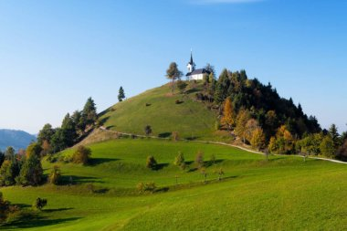 St. Jacob church on top of the hill in the colors of autumn nearing golden hour, Sv. Jakob - Slovenia
