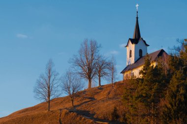 St. Jacob church on top of the hill during golden hour in Slovenia. Religion, hiking, travel and nature concepts.
