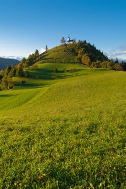 Beautiful countryside scenery with hill and catholic church on top, Sv. Jakob - Slovenia. Religion, hiking and nature concepts
