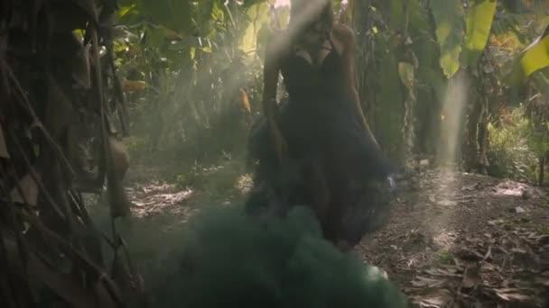Mladá blondýnka v černých šatech a tančí v hustém dýmu u palem a zeleným listím. Sluneční paprsky padají na zem. Bali