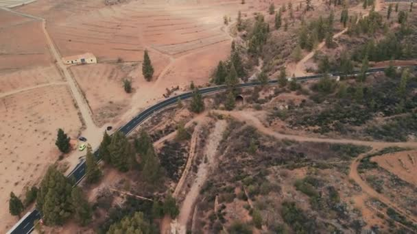 Aerial shot. Tracking cars driving a winding asphalt road leading far into the mountains. Against the background of green trees and red stone desert landscape. Low heapy spectacular clouds in the