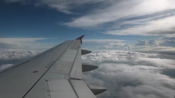 Flight of the plane on a flight level, against the background of blue sky  and textural volumetric clouds  The view from the cockpit of the angle of  view back, in the foreground a gray wing of an