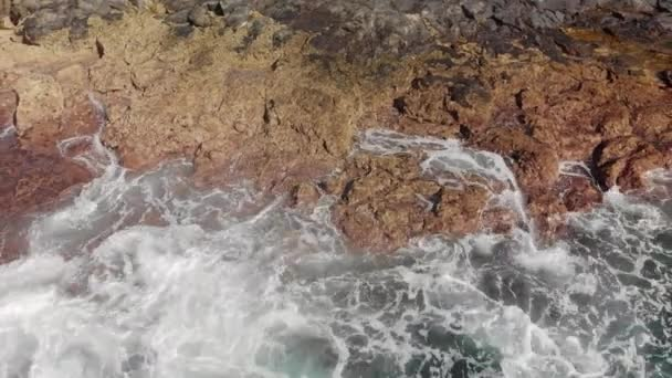 Aerial shot. Turquoise-colored raging ocean waves and volcanic shore. The landscape is large stones of yellow and brown color. Fly on the drone. Close-up