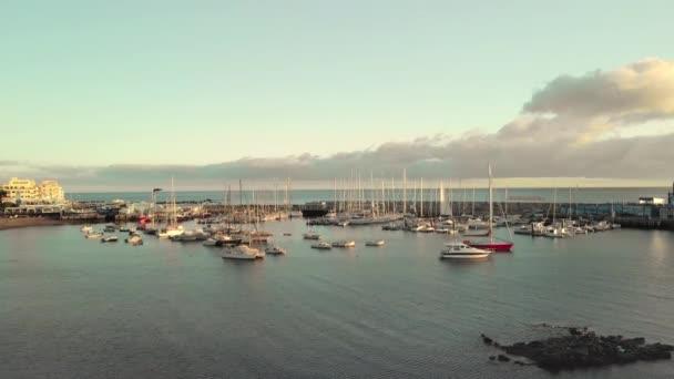 Letecký snímek. Přístav, přístav v malé rybářské město na březích Atlantického oceánu. Velký počet lodí, jachty a čluny při západu slunce. Camera sestup na sopečné pobřeží. V centru
