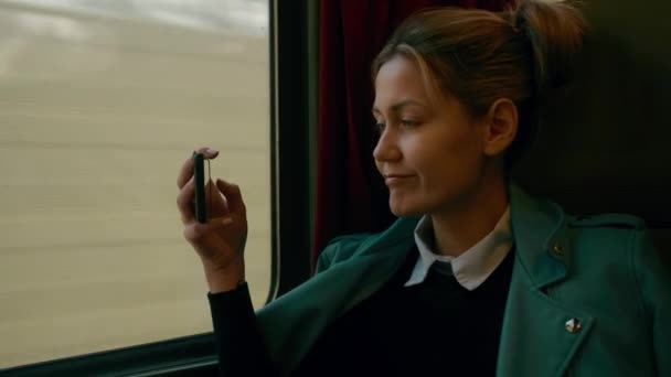 Mladá Kavkazská obchodní žena cestuje v luxusním meziměstském vagónu. Používá mobilní telefon pro fotografie. Uzavření s pomalým pohybem
