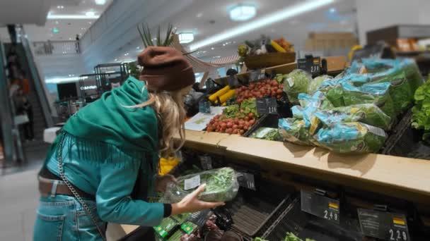 Gyönyörű kaukázusi lány egy kék kabát és egy zöld sálat, dönt és vásárol zöld zöldségek és egészséges termékek a szupermarketben. A koncepció az egészséges táplálkozás és a túlsúly, lassított
