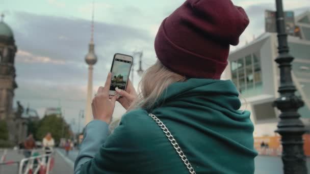 BERLIN, GERMANY - October 2018: Girl tourist photographs on a smartphone sights in the capital of Germany Berlin. Slow Motion In the frame of the Berlin TV Tower and the Cathedral