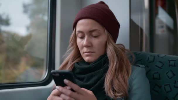 young Caucasian girl in a red cap rides on a subway or tram train car, uses the phone, prints a message. Slow Motion
