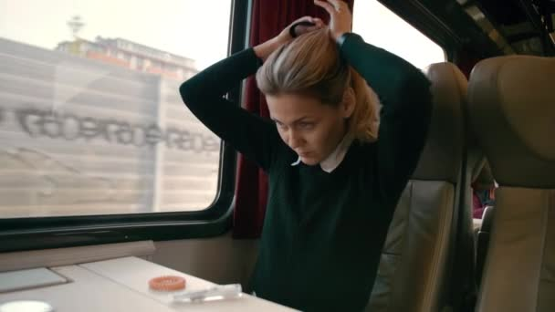 Young caucasian girl rides in a luxury intercity train carriage. Makes a hairstyle out of hair. Concept of how to be beautiful while traveling, slow motion