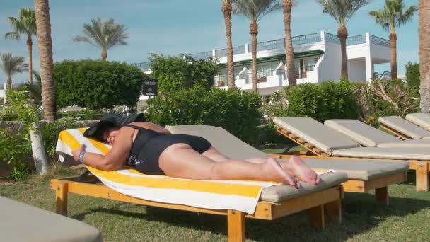 Caucasian senior female elderly in a black hat sunbathes in the sun, lying on a sun lounger. Against the backdrop of a tropical landscape, palm trees and green summer bushes. The concept of recreation