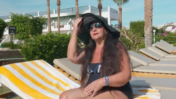 Caucasian senior female elderly in a black hat sunbathes in the sun while sitting on a sun lounger. Against the backdrop of a tropical landscape, palm trees and green summer bushes. Slow Motion