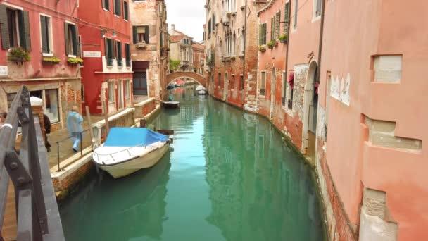 Benátky, Itálie-květen 2019: kanál s krásnou modrou vodou a kotvími čluny a čluny. Několik Italů procházkou úzkými uličkami. Zpomaleně