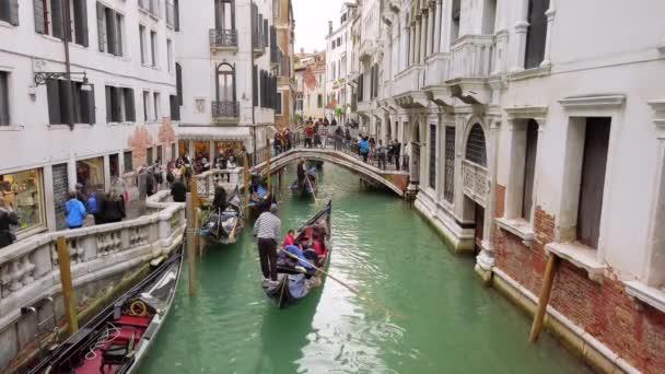 Benátky, Itálie - květen 2019: mnoho turistů na mostě. Úzké kanály - ulice. Gondoly přenášejí turisty. Typická benátská krajina. Zpomalený pohyb