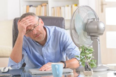 Man suffers from heat while working in the office and tries to cool off by the fan