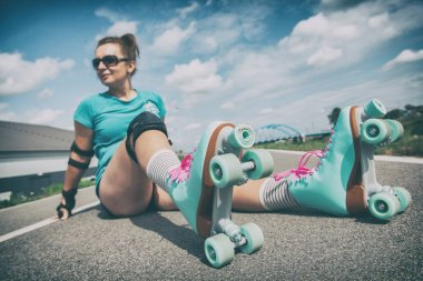 Woman in a vintage roller skates, retro quad roller skates sitting outdoors.
