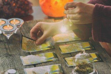 Falcı tarot kartlarının üzerinde sarkacı tutuyor.