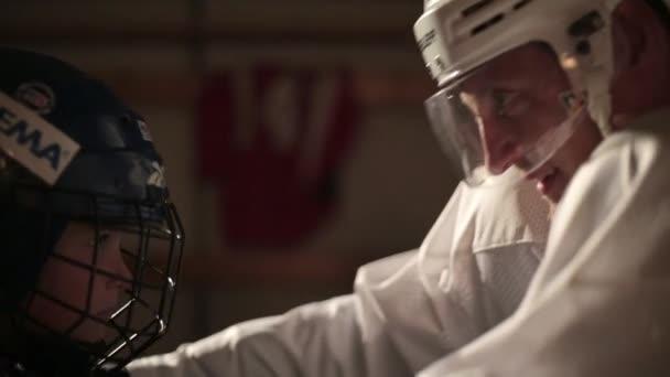 Otec pomáhá jeho syn hokejista nosit uniformu