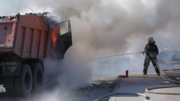 Firefighters extinguish a burning truck with water from the hose