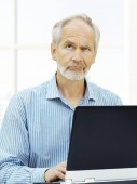 Ältere Mann mit Laptop nachschlagen