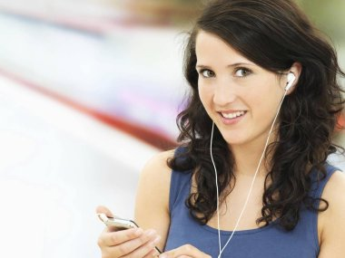 Young woman listening to music on mobile phone and wearing earphones