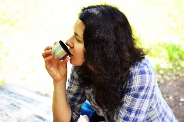 Traveling woman drinks from thermos bottle cap outdoors. Girl rests after hike.