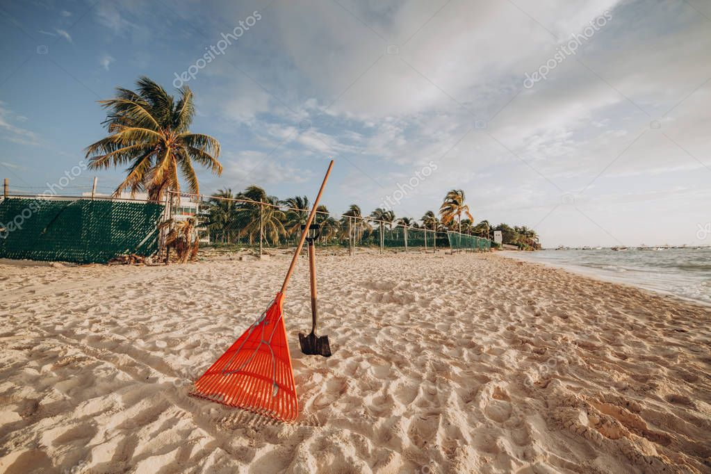 Tools for cleaning the beach. Rake and shovel on sand