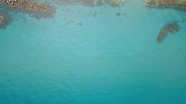 Légifelvételek a tenger partján. Hullámok fröccsenő közelében egy kő strand. Azúr tiszta víz.