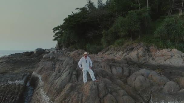 Muž v bílém na sunset beach v Thajsku skály
