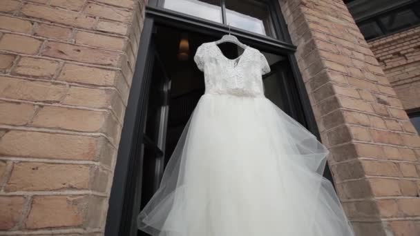 White wedding dress hanging in the aperture windows on the balcony and brick scenes