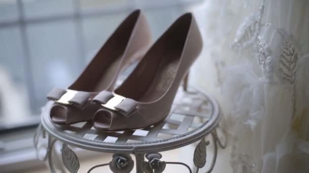 Bílé svatební šaty a boty doma u okna