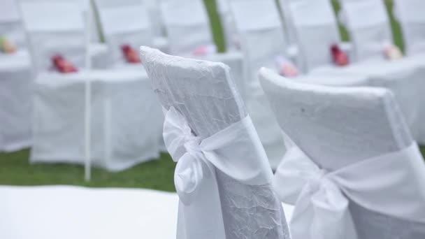 Bílé svatební židle v otevřené obřadu s květy a ornamenty