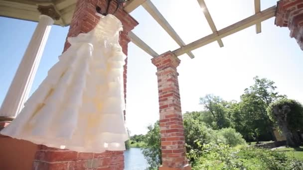 White wedding dress hanging next to a red brick wall in a lazy sunny day before the ceremony