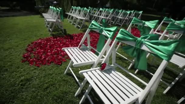 Zelené svatební židle v otevřené obřadu s květy a ornamenty