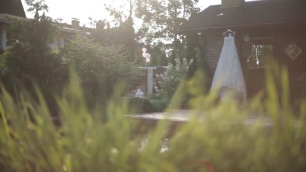 White wedding dress hanging near the wall of the house next to the pool in the sunlight